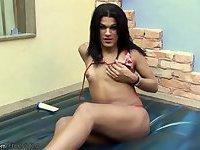 Teen shemale in bikini applies lotion to her growing shecock