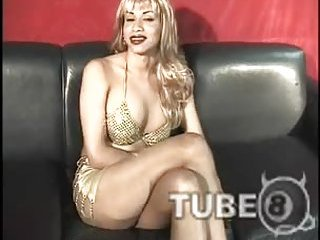 Busty blonde tranny fucks with buddy on the sofa
